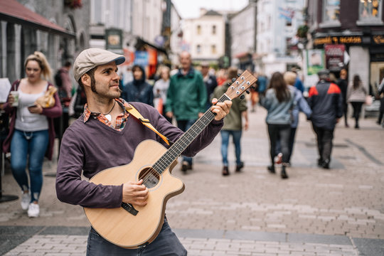 Portrait of a young street performer man playing the guitar on the street.