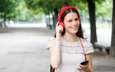 Woman walking in a park while using her smartphone to listen music