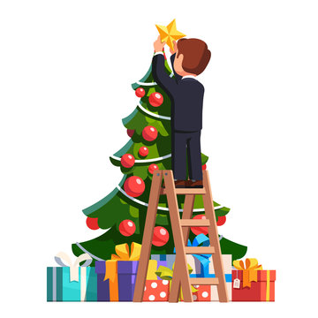 Business man putting star on top of Christmas tree