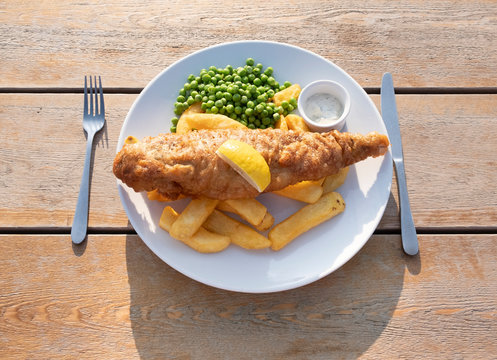 Fish and chips on plate, traditional british food - battered and deep fried cod or haddock