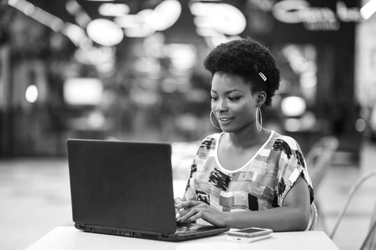 Beautiful Young Dark Skinned Freelancer Woman Using Laptop Computer Sitting At Cafe Table.  Freelance Work Concept.