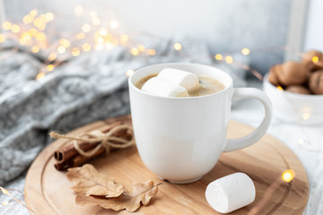Mug with coffee and marshmallow, sweater, cinnamon, decorated with led lights. Autumn mood. Cozy autumn composition. Hygge concept Soft focus - Image