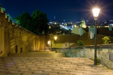 Wall Mural - New castle stairs road leading up to Prague Castle Czech Republic enlightened by street lamps with a beautiful view over Prague during night