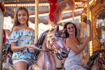 Happy family (mother and daughter) at the carousel. Merry go round horse with colorful lights