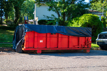 Red dumpster with black plastic liner on a asphalt street near the side of a house
