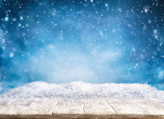 Fototapeta Beautiful winter background with wooden old desk and blurred blue sky. Winter, New Year and Christmas concept with snowy background.