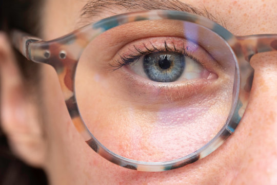 close up on young girl blue eye wearing with corrective lens glasses