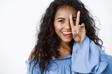 Close-up playful and feminine coquettish, african-american curly-haired female in blue blouse, silly showing tongue, make peace, goodwill sign over face, having fun and joking with positive emotions