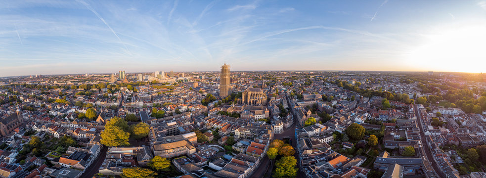 Wide panoramic aerial view of the medieval Dutch city centre of Utrecht with cathedral towering over the city at early morning sunrise. Cityscape in The Netherlands