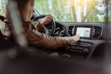Woman girl in summer car interior in forest park, selects navigation touch screen, satellite internet application. Lost in search of a route, parking in the fresh air rest in the forest.