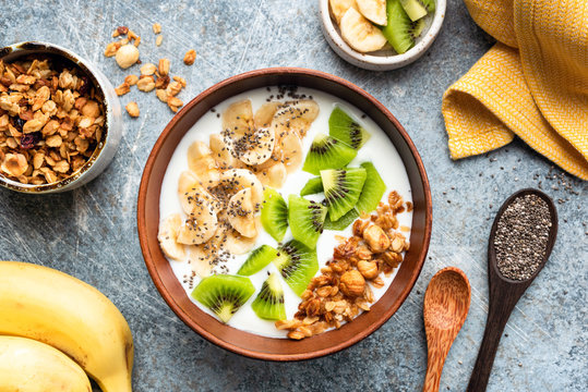 Healthy breakfast smoothie bowl with granola, fruits and yogurt. Top view. Clean eating, dieting, weight loss concept