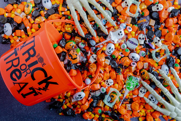 Halloween candy spilling out of orange trick or treat bucket Wall mural