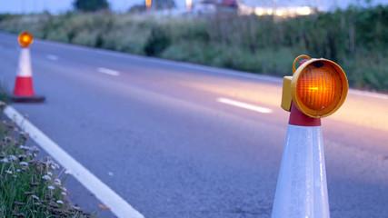 roadworks cone flashing on UK motorway at night with traffic passing