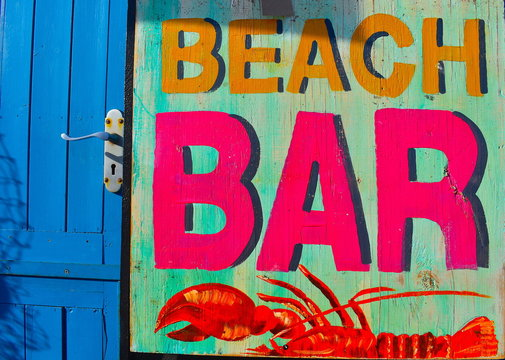 Vintage neon blue, pink, yellow and orange wooden lobster shack sign. Hastings, Sussex, English coast