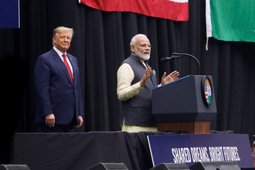 """U.S. President Donald Trump looks on as Indian Prime Minister Narendra Modi speaks during a """"Howdy, Modi"""" rally at NRG Stadium in Houston, Texas"""