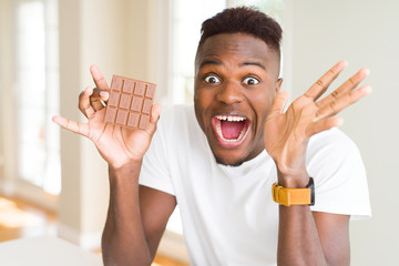 Young african american man eating chocolate bar very happy and excited, winner expression celebrating victory screaming with big smile and raised hands