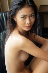 Philippine woamn posing nude in a black chair