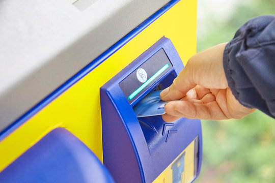 A female hand takes a plastic card from an ATM slot. The concept of safe use of bank cards, money transfers, payment for services and goods, receipt of cash. Close-up