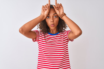 Young brazilian woman wearing red striped t-shirt standing over isolated white background doing funny gesture with finger over head as bull horns