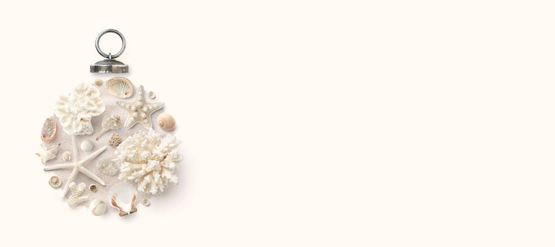 Christmas in July / at the beach / in the southern hemisphere conceptual banner, background or header / hero image with holiday ornament made of shells, starfish and corals, flat lay, copyspace