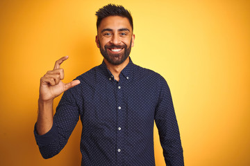 Young handsome indian businessman wearing shirt over isolated yellow background smiling and confident gesturing with hand doing small size sign with fingers looking and the camera. Measure concept.