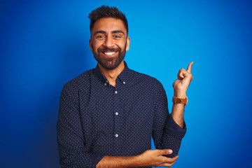 Young indian elegant man wearing shirt standing over isolated blue background with a big smile on face, pointing with hand and finger to the side looking at the camera.