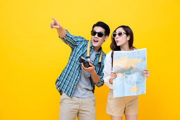 Excited tourist couple holding map and pointing