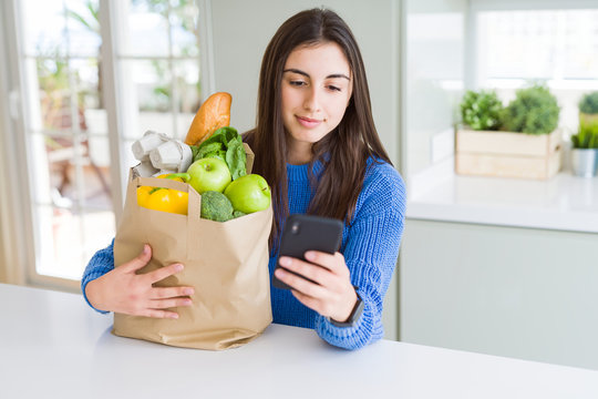 Young woman holding a paper bag full of fresh groceries and using smartphone app for supermarket delivery