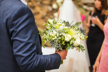 Close up image of caucasian groom in suit holds wedding bouquet in arm in selective focus.