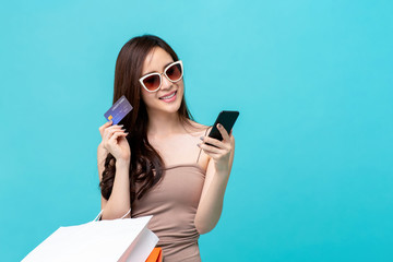 Woman holding bags and credit card using phone