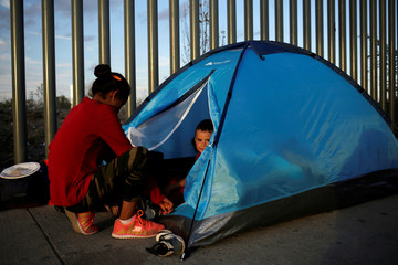 A Mexican citizen fleeing violence camps in a queue with a child to try to cross into the U.S. to apply for asylum at Cordova-Americas border crossing bridge in Ciudad Juarez