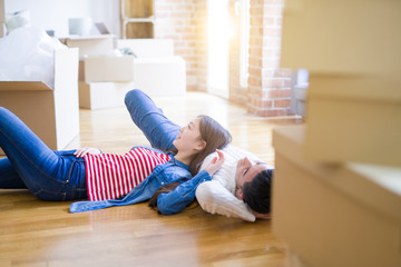 Young asian couple lying on the floor of new house arround cardboard boxes relaxing and smiling happy