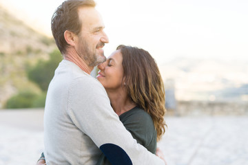 Obraz Romantic couple smiling,  cuddling and hugging on a sunny day - fototapety do salonu