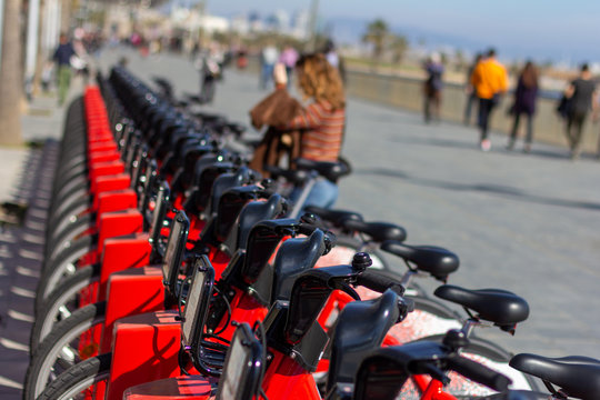 Barcelona, Spain - February 26, 2019 - Red bicycles belonging to the public transportation sharing service Bicing line the boardwalk in the Barcelonetta neighborhood