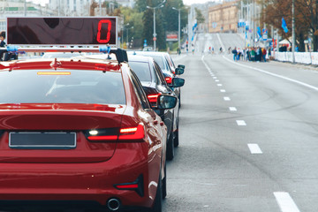 Car is in the row of cars to accompany the participants of the marathon is at the start