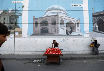 An Afghan boy sells pomegranates along a street in Kabul, Afghanistan