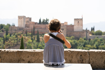 Little girl making photo with DSLR camera to the Alhambra.