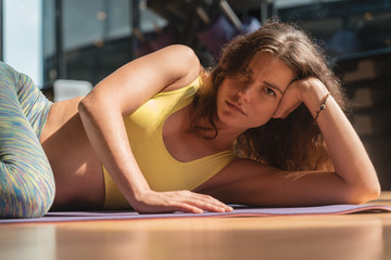 Portrait image of a woman wearing yoga clothes lying at a fitness facility