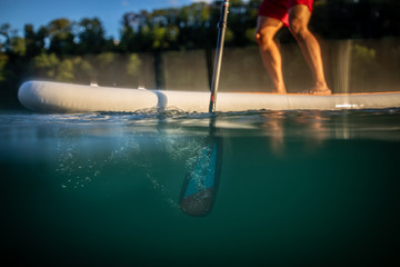 Young man on a paddle board. Getting a great exercise on a lovely river in warm evening sunlight - paddle underwater image