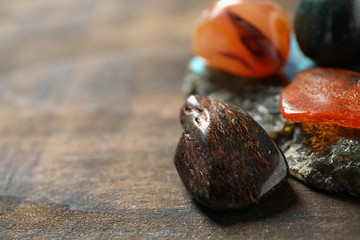 Different beautiful gemstones on wooden table, closeup