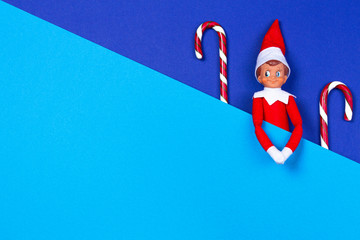 Christmas background. Little toy elf and candy canes on multicolored blue and light blue background. Top view