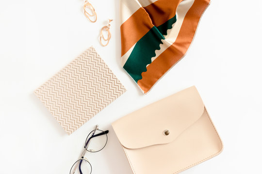 Fashion flat lay of handbag, earrings, notepad, glasses and scarf on white desk