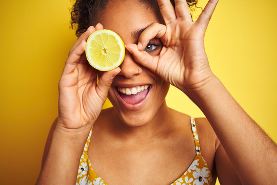Young african american woman holding slice of lemon over isolated yellow background with happy face smiling doing ok sign with hand on eye looking through fingers