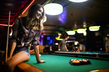 Young beautiful girl is playing billiards. Pleasant pastime, rest, entertainment.