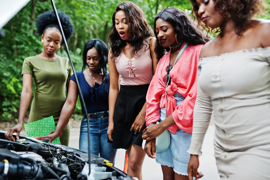 Group of five african american traveler girls looking at broken car open hood.