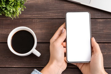 Woman using blank smartphone and drinking coffee at workplace