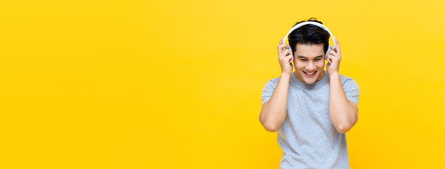Happy Asian man wearing headphones listening to love song