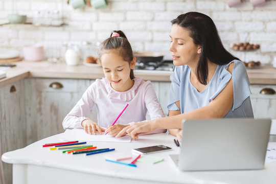 Little girl having lessons with tutor at home