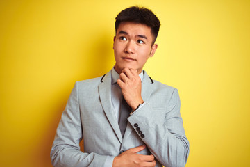 Asian chinese businessman wearing suit and tie standing over isolated yellow background with hand on chin thinking about question, pensive expression. Smiling with thoughtful face. Doubt concept.