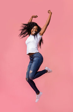 Smiling young african woman jumping in air